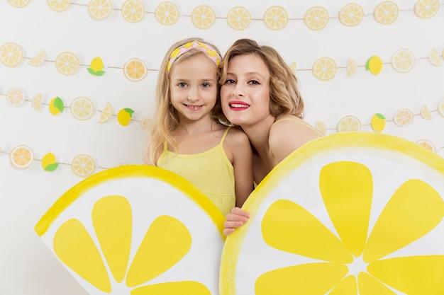 女性と少女のレモン装飾でポーズ