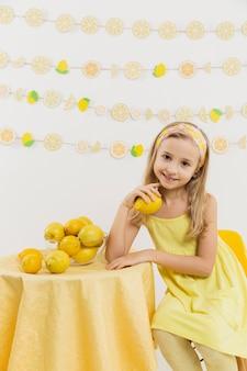 レモンを押しながら笑顔の幸せな女の子の正面図
