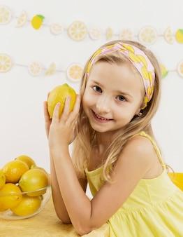レモンを押しながらポーズをとって笑顔の女の子の正面図