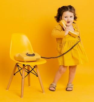 Милый ребенок позирует, держа телефон