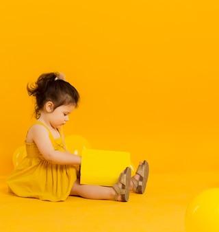 Вид сбоку ребенка позирует с книгой и копией пространства