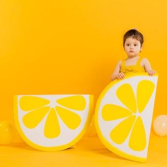 Вид спереди ребенка позирует с украшениями ломтиками лимона