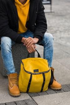 Крупным планом парень сидит с желтым рюкзаком