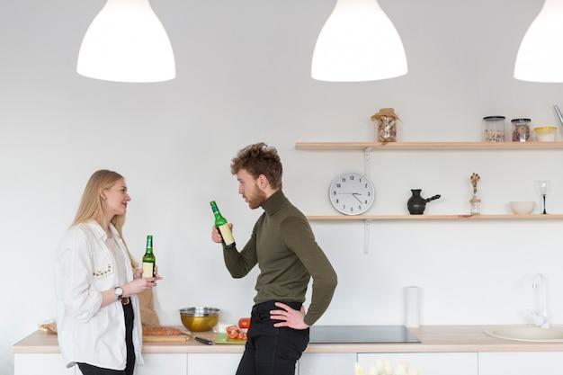 Боковой вид мужчина и женщина, наслаждаясь пивом вместе