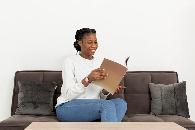 本とソファの上の肖像画の女性