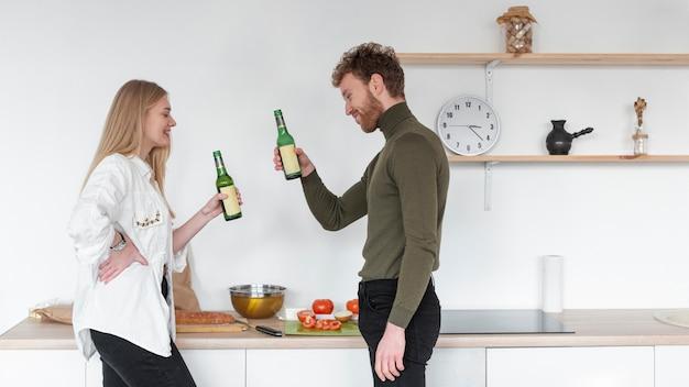 女と男のビールの瓶を楽しんで