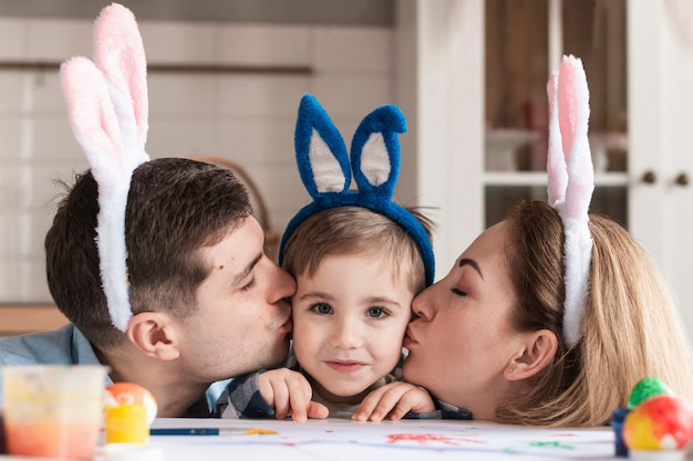 Макро отец и мать целуют маленького мальчика