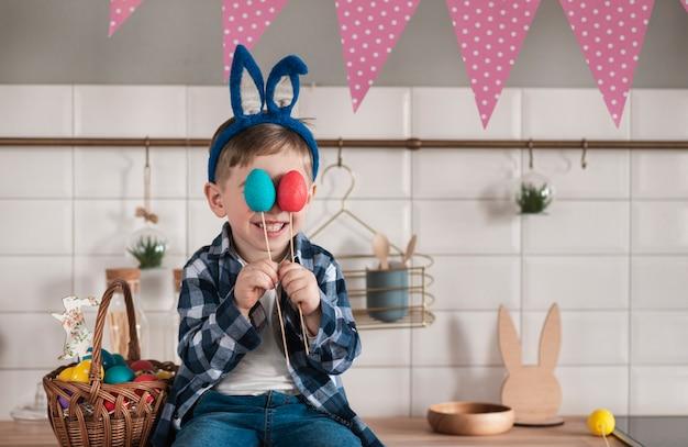 Портрет прелестный маленький мальчик держит пасхальные яйца