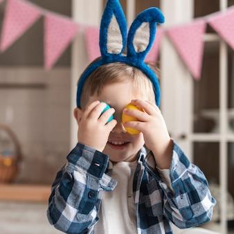 Портрет прелестный маленький мальчик, играя с пасхальными яйцами