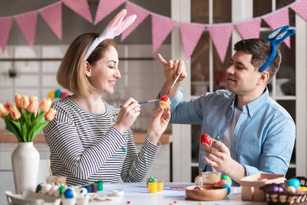 Мать и отец играют с краской