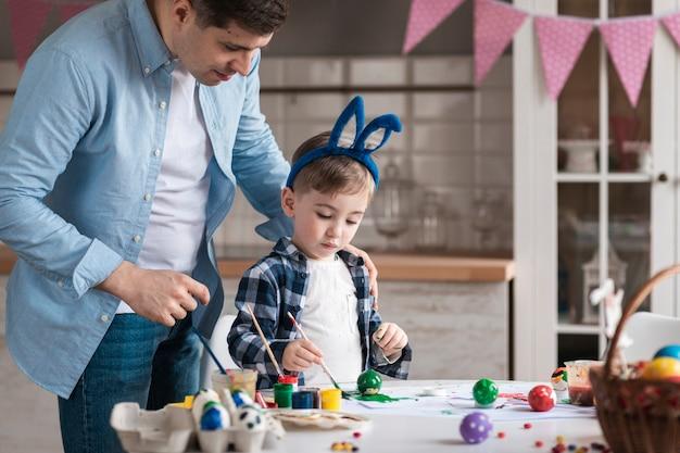 Отец учит маленького мальчика, как рисовать яйца на пасху