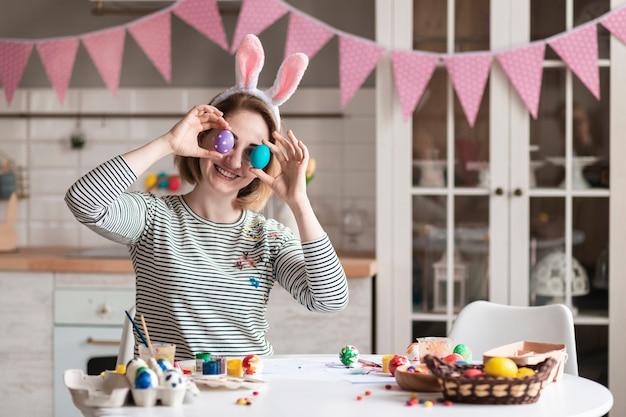 Милая взрослая женщина играет с пасхальными яйцами