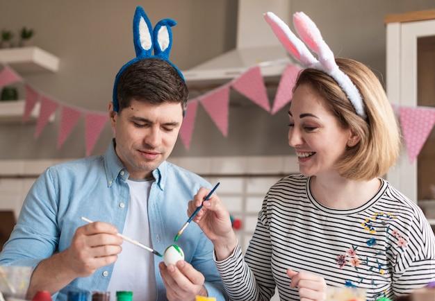 Очаровательный отец и мать красят яйца на пасху