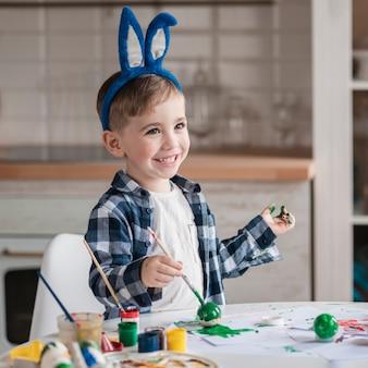 Портрет прелестный маленький мальчик, играя с краской