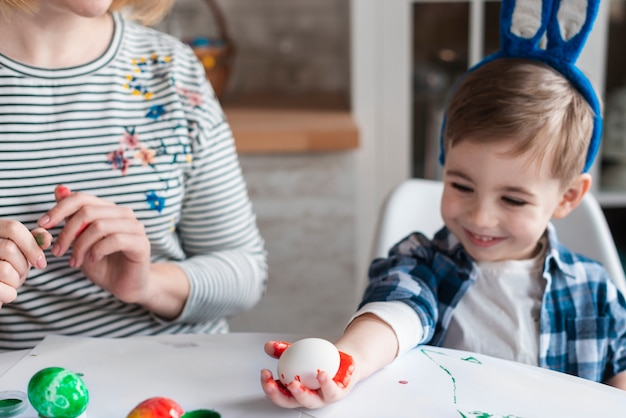 Милый маленький мальчик с ушками зайчика держит яйцо