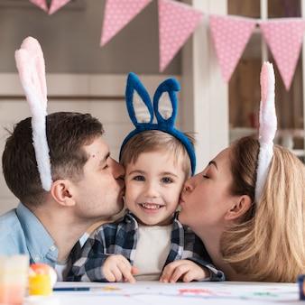 母と父の愛らしい小さな男の子にキス