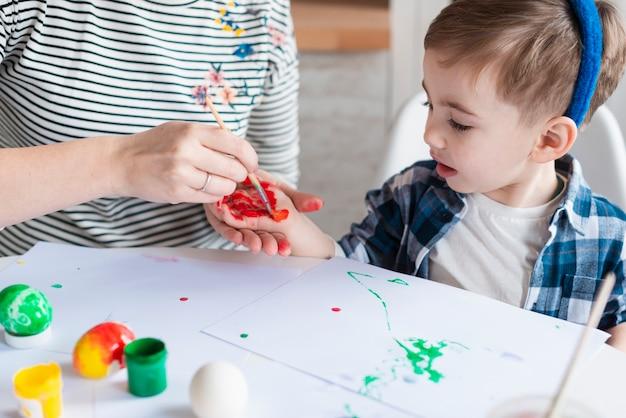 Мать крупного плана крася руку маленьких мальчиков
