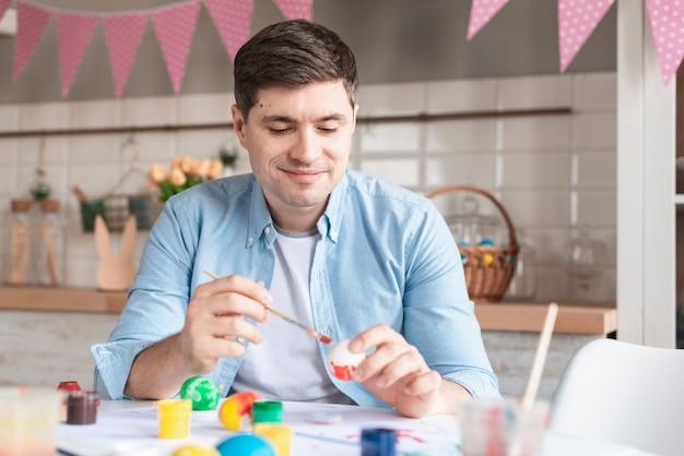 Портрет положительного отца красит яйца на пасху