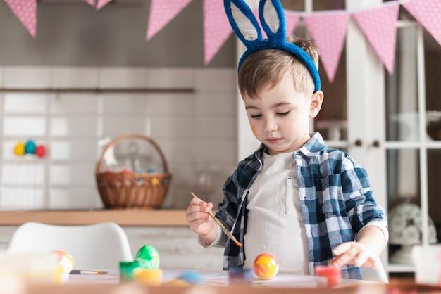 イースターのための愛らしい小さな男の子絵画卵の肖像画