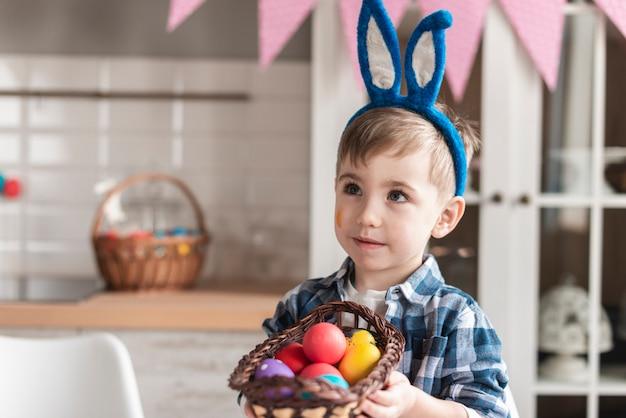 卵のバスケットを持って愛らしい男の子の肖像画