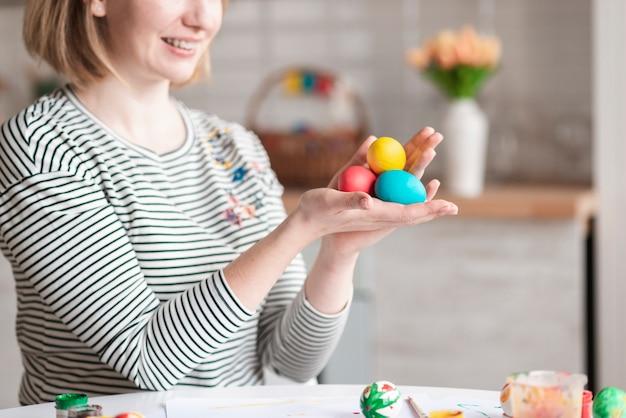 Крупным планом женщина держит пасхальные яйца