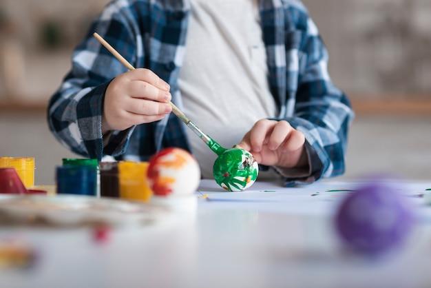 イースターのためのクローズアップの小さな男の子絵画卵