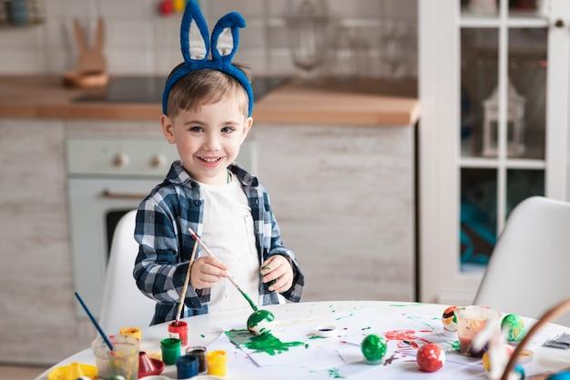 イースターのための愛らしい小さな男の子絵画卵