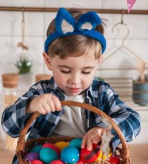 Прелестный маленький мальчик, играя с пасхальными яйцами