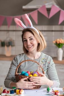Портрет очаровательны женщина, держащая корзина с пасхальными яйцами