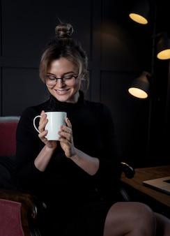 彼女のコーヒーカップに満足して自信を持って若い女性