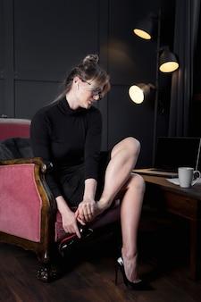 Успешная деловая женщина снимает обувь