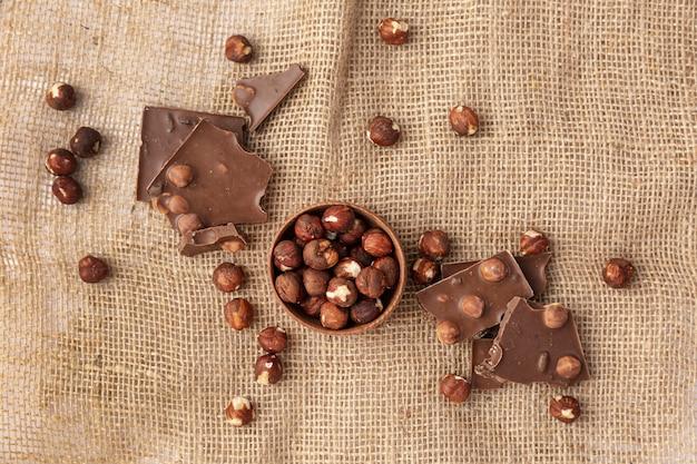 Вид сверху шоколада с фундуком на мешковине