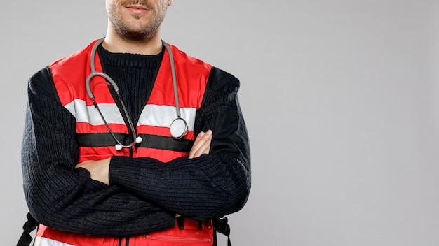組んだ腕とコピースペースを持つ男性の救急救命士