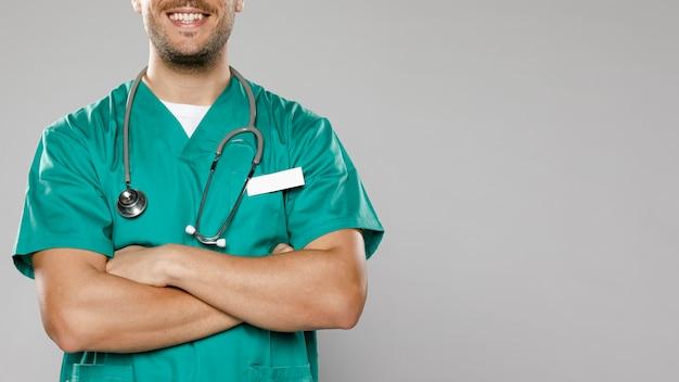 組んだ腕を持つスマイリー男性医師