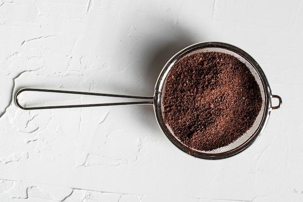 Плоско положите порошок кофе в ситечко