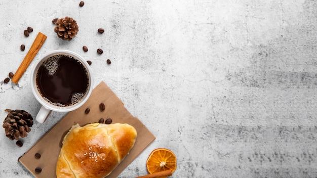 一杯のコーヒーとクロワッサンをコピースペースで平らに置く