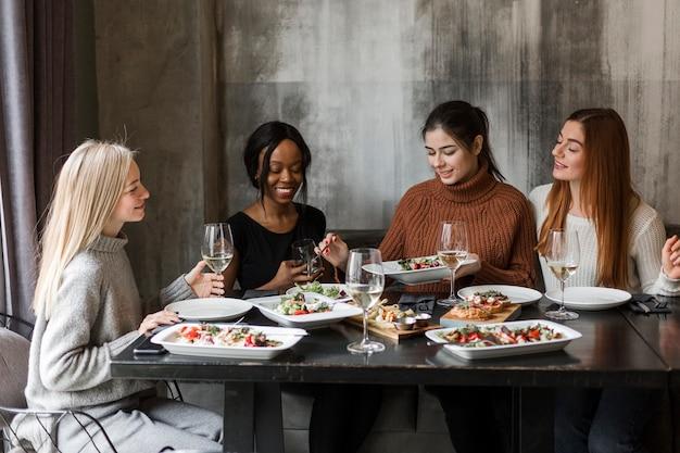 夕食とワインを一緒に持っている若い女性のグループ