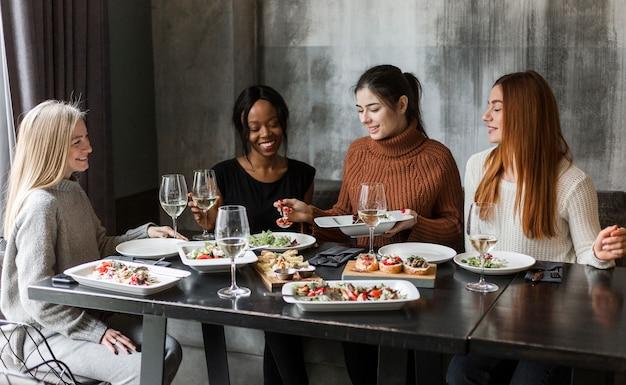 一緒に夕食を楽しんでいる美しい女性のグループ