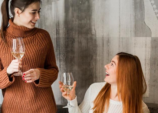 Группа молодых девушек с напитками улыбается