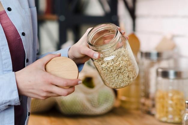 穀物が付いている瓶を保持しているクローズアップの女性