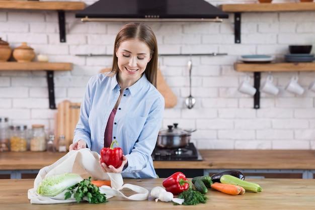 Положительная молодая женщина гордится органическими овощами