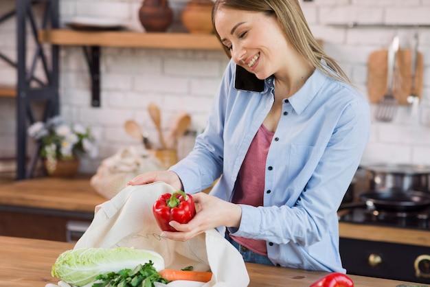 Красивая молодая женщина достает продукты из сумки