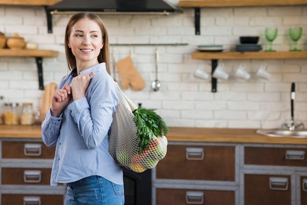Портрет молодой женщины, держащей многоразовую сумку с продуктами