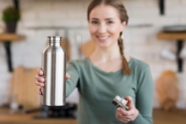 Портрет улыбающейся молодой женщины, держащей термос