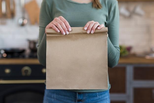 紙袋を保持しているクローズアップの若い女性