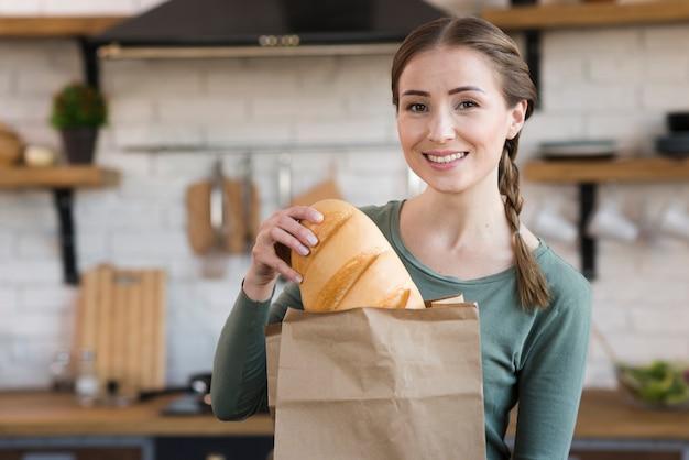 焼きたてのパンを保持しているスマイリーの若い女性