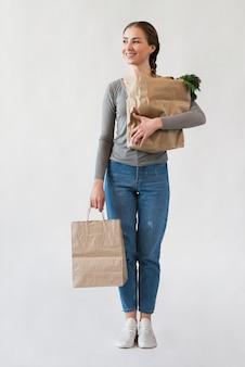 Портрет молодой женщины, держащей бумажные пакеты с продуктами