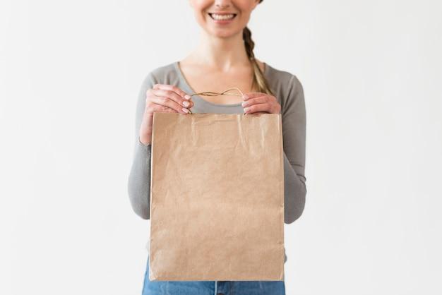 食料品の紙袋を保持しているクローズアップの女性