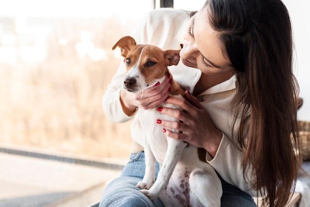 女性の飼い主が持っている愛らしい犬