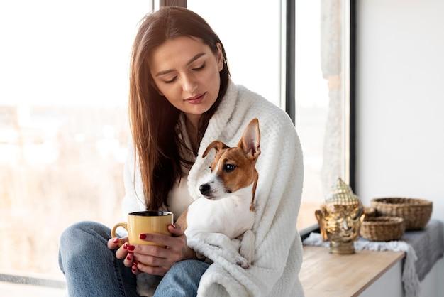 Женщина держит кружку и собаку на коленях